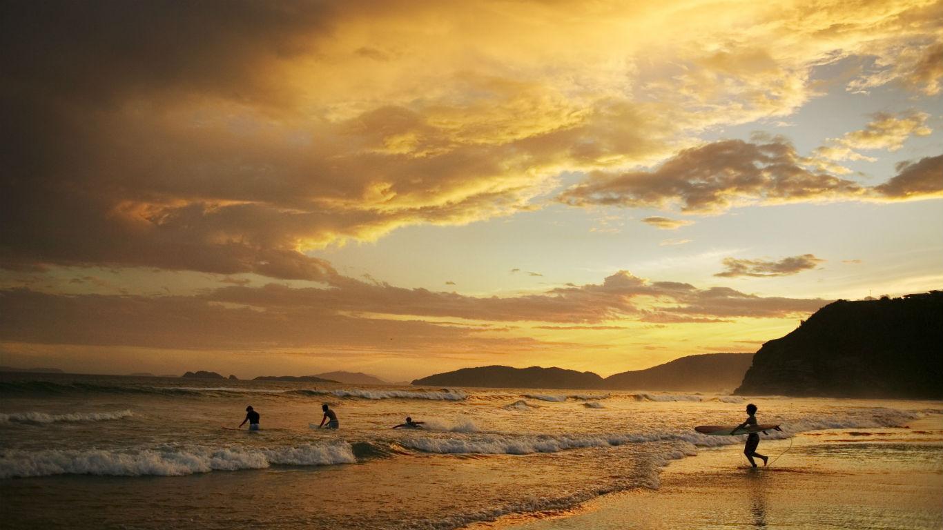 巴西布希奥斯,黄昏时分海岸边的冲浪者